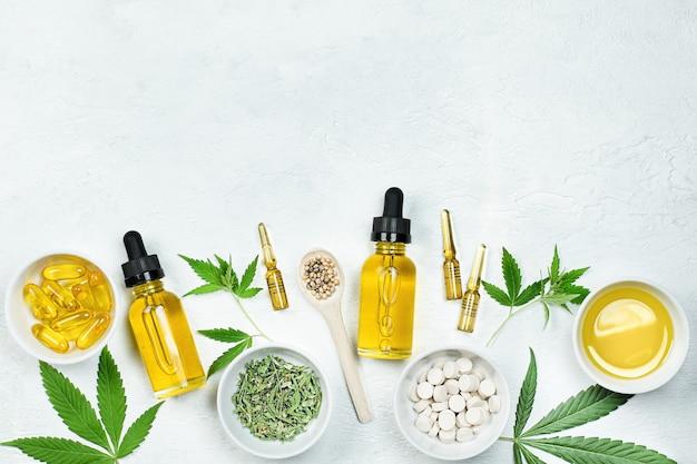 Huile de cbd, ampoules, capsules et comprimés avec des feuilles de cannabidiol et de cannabis sur une table en béton gris