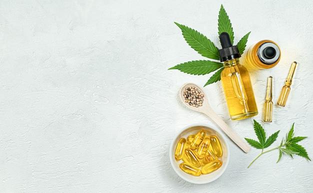 Huile de cbd, capsules, ampoules, graines et feuilles de cannabis fraîches sur fond de béton gris vue de dessus