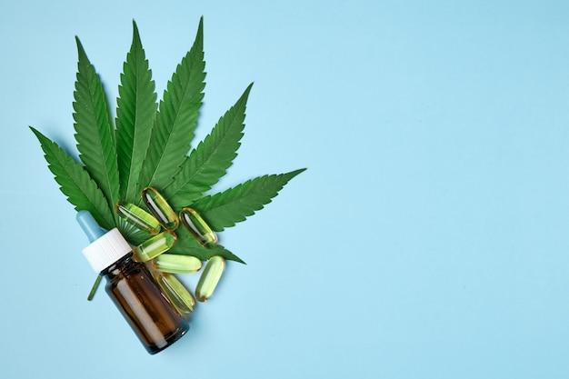 L'huile de chanvre de cannabis cbd dans une capsule ou des pilules et une bouteille posée sur la feuille de marijuana verte fraîche