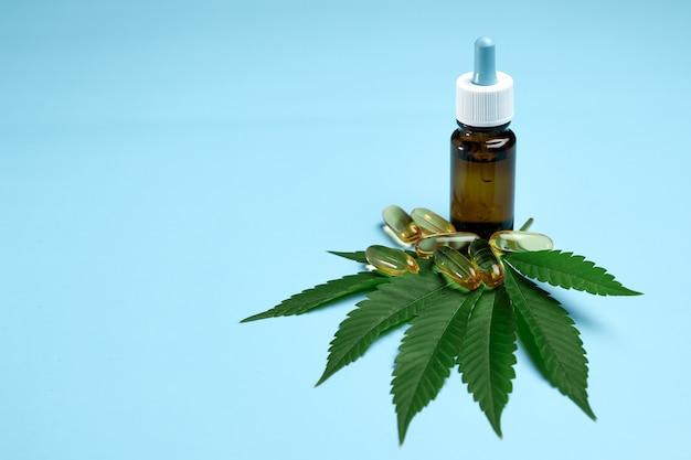 L'huile de chanvre de cannabis cbd dans une pilule et une bouteille sur la feuille de marijuana verte sur le bleu
