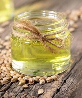 L'huile de chanvre dans un bocal en verre et des grains de cannabis sur fond de vieilles planches de bois close-up.