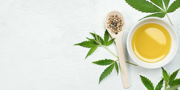 Huile de chanvre, feuilles et graines de cannabis sur une table blanche, vue de dessus
