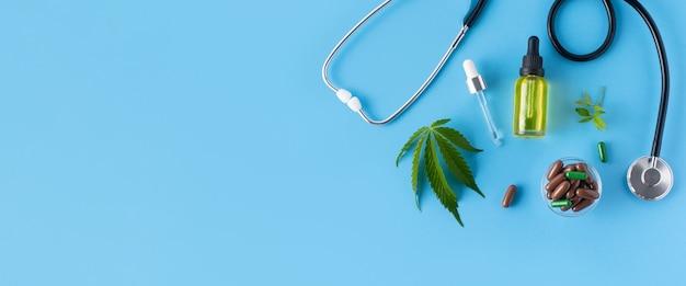 Huile de chanvre, pilules, feuilles de cannabis, stéthoscope sur fond bleu avec espace de copie. notion médicale. bannière