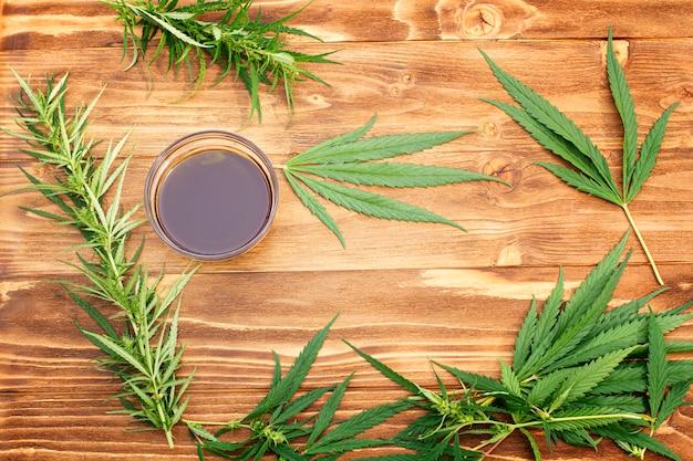 L'huile de chanvre. une tasse d'huile de chanvre avec des feuilles de chanvre sur une table en bois marron.