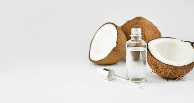 L'huile de coco dans une bouteille de noix de coco sur un tableau blanc. concept de soins de la peau. cosmétiques pour le visage. copiez l'espace.