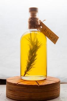 L'huile de coco dans une bouteille en verre sur une planche blanche et en bois. vue de côté.