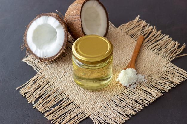 L'huile de coco dans un pot et les noix de coco fraîches sur une surface sombre. cosmétiques naturels.