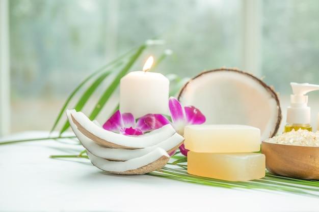 Huile de coco, feuilles tropicales et noix de coco fraîches. produits de noix de coco spa sur une surface en bois clair.