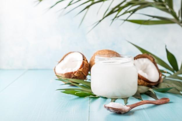 L'huile de coco et les noix de coco sur un pastel brillant, mise au point sélective.