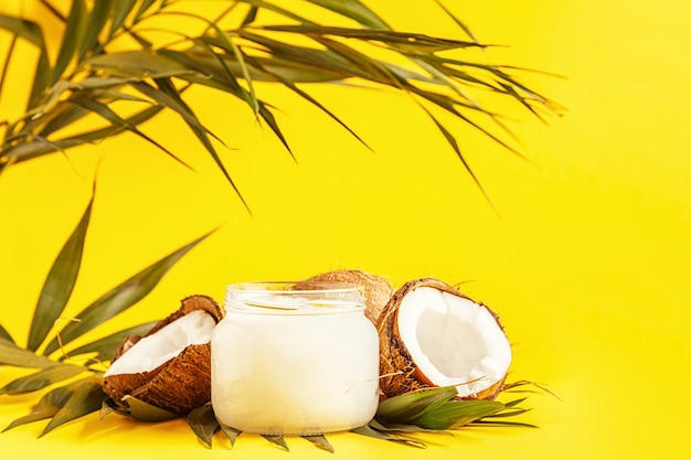 Huile de coco et noix de coco sur un pastel vif