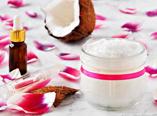 L'huile de coco et les noix de coco pour une thérapie alternative sur une surface blanche en bois