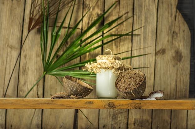 L'huile de coco avec des noix fraîches sur la vieille table en bois