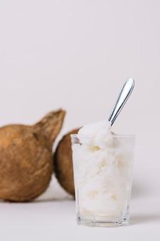 Huile de coco à la verticale avec des noix de coco