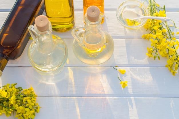 L'huile de colza sur table en bois blanc