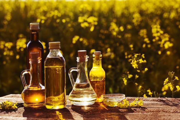 L'huile de colza sur table en bois dans le champ