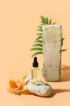 Huile cosmétique de beauté ou extraction en bouteille en verre sur podium en pierre décorée de fleurs fraîches et de fougère végétale sur espace beige