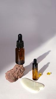 Huile cosmétique en bouteille en verre sur fond blanc avec des ombres à la mode. concept zéro déchet