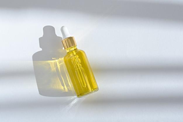 Huile cosmétique en bouteille en verre avec pipette blanche sur fond blanc avec espace copie