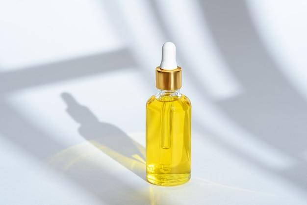 Huile cosmétique en bouteille en verre avec pipette sur fond blanc avec ombre, concept de bien-être écologique