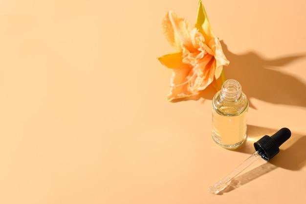 Huile cosmétique ou essence en bouteille en verre avec des fleurs de lys fraîches sur espace beige