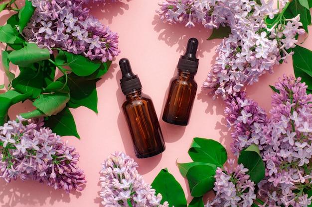 Huile cosmétique et lilas sur fond rose. un récipient pour l'huile cosmétique. cosmétologie. soin de la peau .
