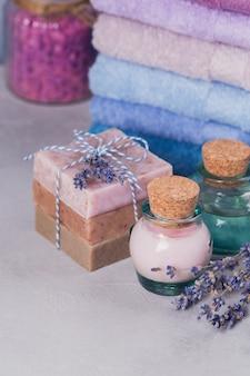 Huile cosmétique naturelle, crème, sel de mer et savon artisanal naturel à la lavande sur fond clair. soins de la peau saine. concept d'aromathérapie, de spa et de bien-être