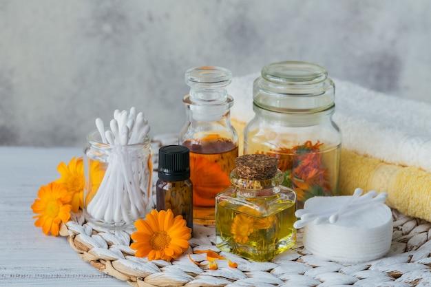 Huile cosmétique naturelle, huile essentielle, teinture ou infusion, coton, bâtonnets et serviettes aux fleurs de calendula sur une lumière