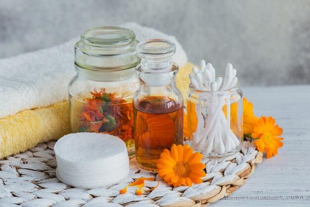 Huile cosmétique naturelle, teinture ou infusion, coton, bâtonnets et serviettes aux fleurs de calendula sur une lumière. soins de la peau en bonne santé. concept d'aromathérapie, spa et bien-être
