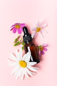 Huile cosmétique ou parfum ou médicament en verre brun avec pipette et fleurs