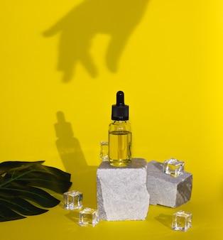 Huile cosmétique pour cheveux ou visage dans un flacon en verre avec une pipette. soins du corps, spa. couleurs tendances, ombres et glaçons.