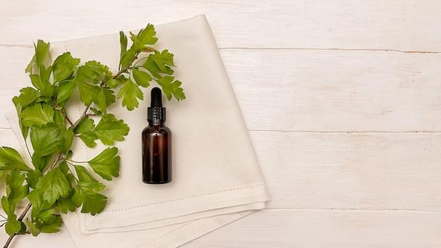 Huile cosmétique pour les soins du visage et du corps. sur fond blanc. feuilles vertes.
