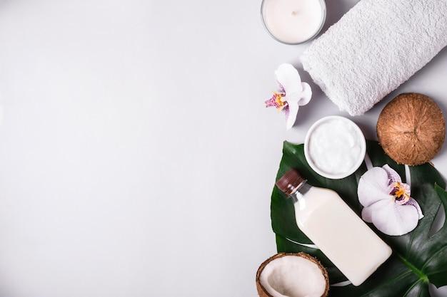 Huile et crème de noix de coco, feuilles et fleurs tropicales. concept de spa naturel.