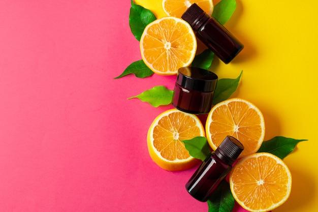 Huile essentielle d'agrumes. agrumes en tranches et bouteilles d'arôme sur fond rose