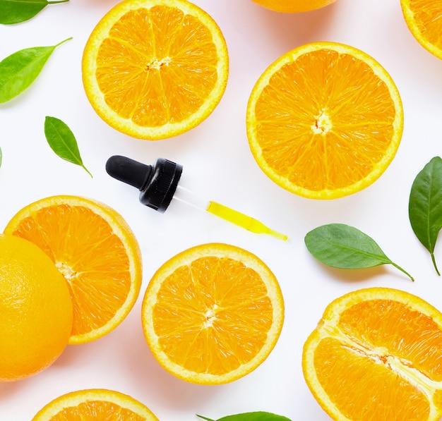 Huile essentielle d'agrumes avec des fruits orange frais isolé sur blanc