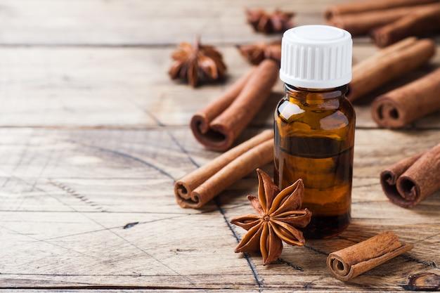 Huile essentielle aromatique avec cannelle et anis étoilé sur bois. mise au point sélective.