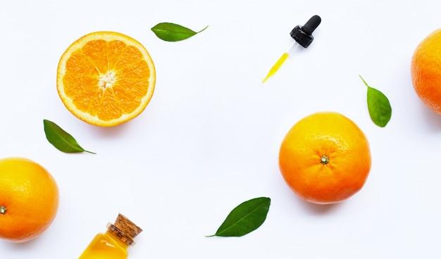 Huile essentielle aux oranges sur blanc.