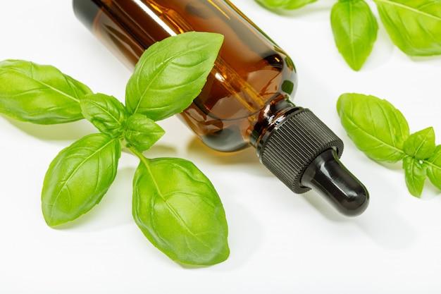 Huile essentielle de basilic isolé sur blanc. huile de basilic pour les soins de la peau, l'aromathérapie et la médecine naturelle