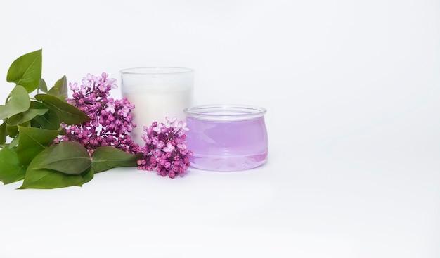 Huile essentielle, bougie aromatique blanche et une branche de lilas sur fond blanc.