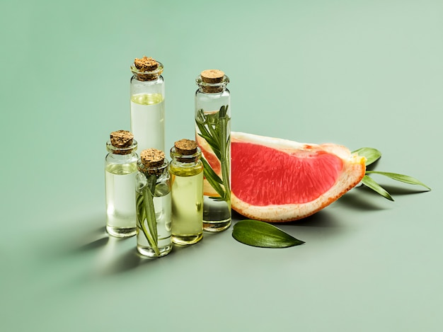 Huile essentielle en bouteille en verre avec pamplemousse frais et juteux et traitement de beauté aux feuilles vertes.