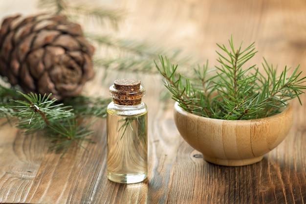 Huile essentielle de cèdre dans une bouteille en verre. flou artistique fond en bois