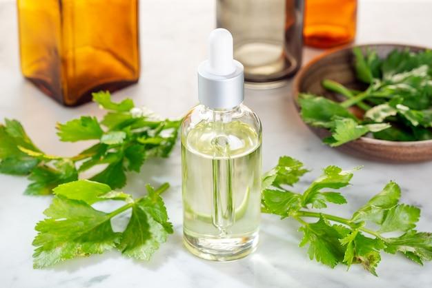 Huile essentielle de céleri. huile de céleri sur une bouteille en verre avec compte-gouttes