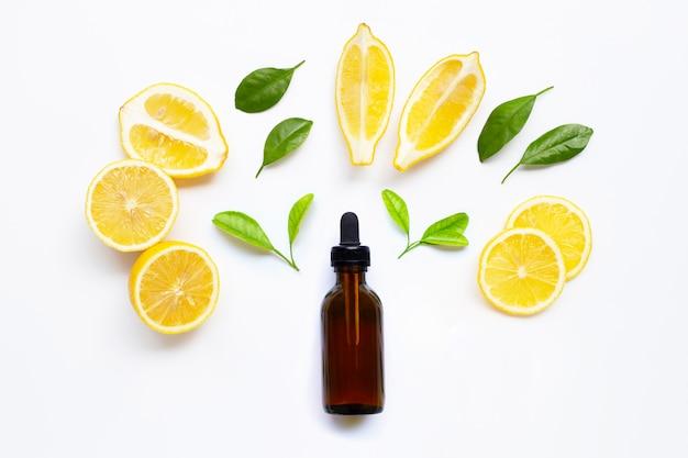 Huile essentielle de citron frais et de feuilles vertes sur blanc
