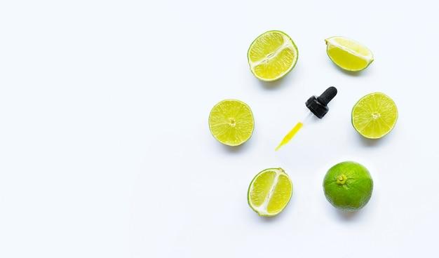 Huile essentielle de citrons verts sur blanc avec fond