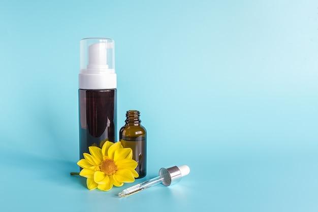 Huile essentielle dans un petit flacon compte-gouttes brun ouvert avec une pipette en verre couchée, une grande bouteille avec un distributeur blanc et une fleur jaune