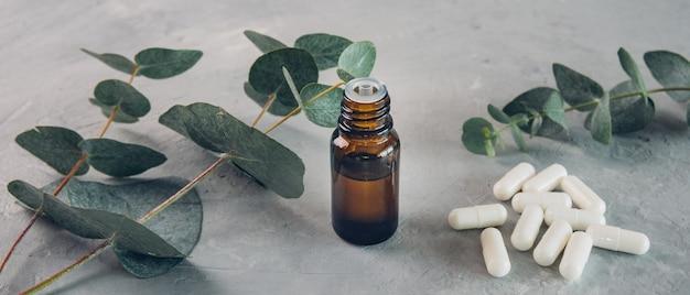 Huile essentielle d'eucalyptus et feuilles fraîches, comprimés de capsules blanches sur planche de pierre.