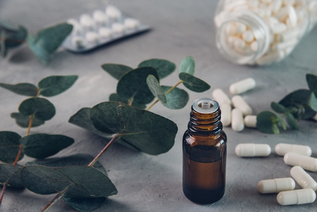 Huile essentielle d'eucalyptus et feuilles fraîches, pilules de capsules blanches sur la planche de pierre.