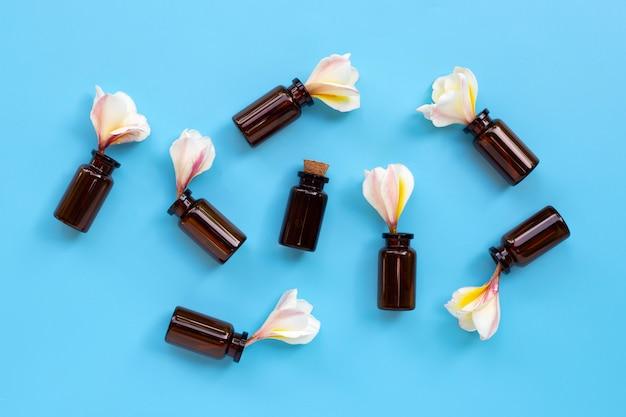 Huile essentielle de fleur de plumeria ou de frangipanier sur fond bleu.