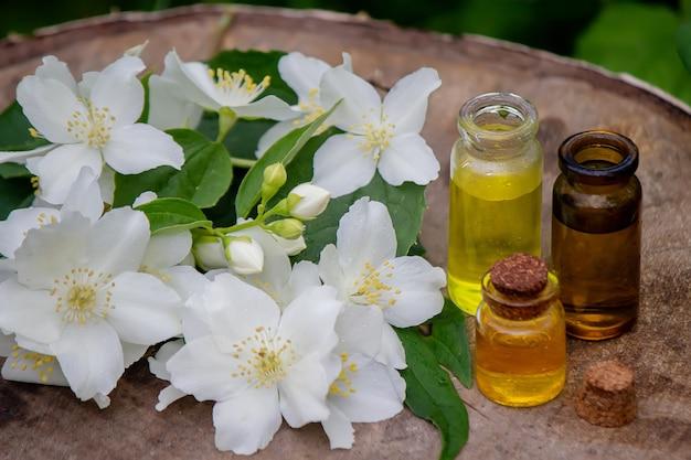 Huile essentielle et fleurs de jasmin sur un fond en bois. procédures cosmétiques. mise au point sélective