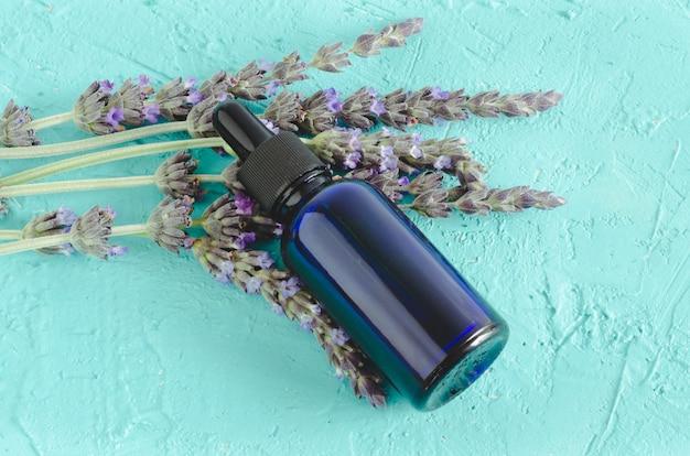Huile essentielle de lavande. fleurs et bouteille avec pipette sur surface bleue
