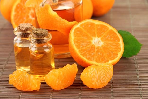 Huile essentielle de mandarine et mandarines sur tapis de bambou gris